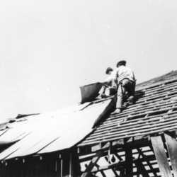 Unknown individuals working on a roof of barn